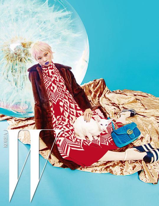 퍼 코트, 지오메트릭 프린트의 롱 드레스, 크림색 타이츠, 줄무늬가 돋보이는 플랫폼 웨지힐 샌들, 반지, 푸른색 벨벳 소재의 GG 마몽(Marmont) 2.0 백은 모두 Gucci 제품.