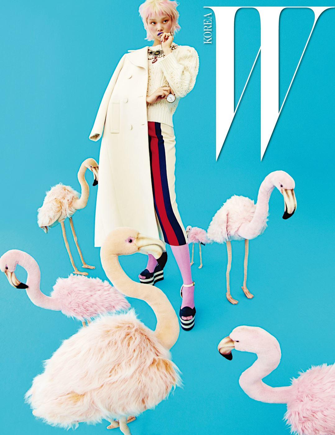 순백의 테일러드 롱 코트, 진주 장식 니트 톱, 줄무늬 스커트, 분홍색 타이츠, 플랫폼 샌들, 반지는 모두 Gucci 제품.