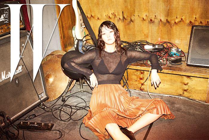 팔 부분의 줄 장식이 특징인 스웨터와 낭만적인 주름 스커트, 중성적인 슈즈는 모두 Obzee 제품.