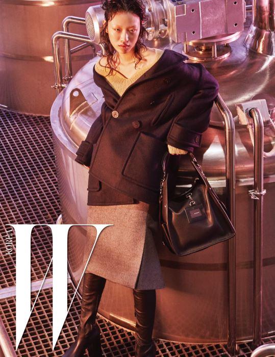 남색 스윙 피 코트, 베이지색 하트넥 니트 톱, 모직 소재의 회색 킥 스커트, 검정 플랫폼 사이하이 부츠, 검은색 툴 숄더백은 모두 Balenciaga 제품.
