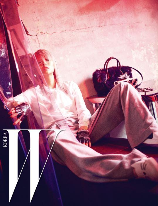 시폰 소재의 리본 블라우스, 통이 넓은 회색 팬츠, 체인 장식의 가죽 장갑, 고양이가 그려진 하얀색 슬립온 슈즈, 책상에 놓인 퍼 쇼퍼백, 스타투스 패턴의 아크릴 클러치는 모두 Karl Lagerfeld 제품.