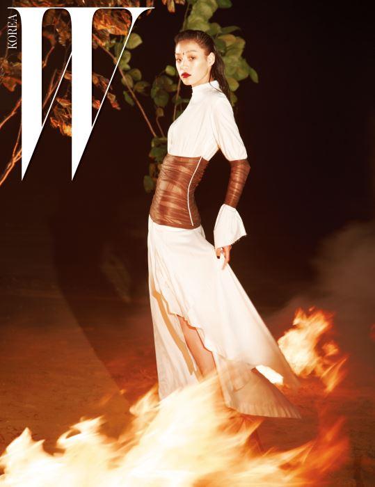 허리와 팔에 부드러운 튤로 포인트를 준 하얀색 코튼 드레스는 Loewe 제품.