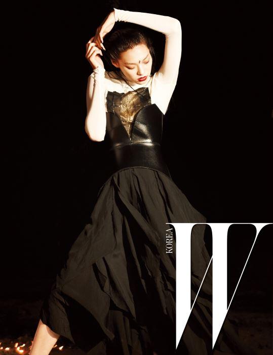 추상 작품이 연상되는 패턴이 그려진 하얀색 톱과 가죽 뷔스티에, 검은색 주름 스커트는 Loewe 제품.
