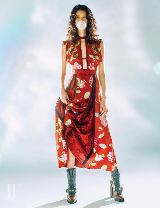 꽃무늬 드레스의 주름 사이로 뱀피 프린트를 섞은 독특한 미디 드레스와 펀칭 벨트 장식 레이스업 부츠는 모두 Burberry 제품.