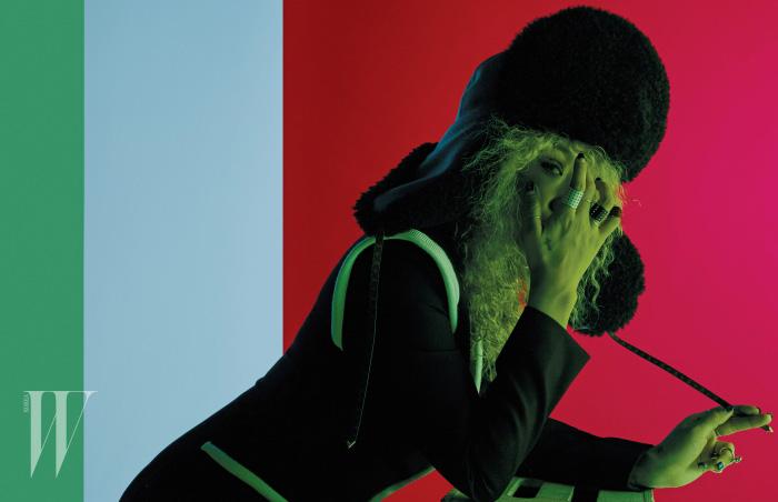 안감에 퍼 장식을 더한 모노그램 가죽 모자와 라이닝이 돋보이는 톱, 가죽 밴드 링은 모두 Louis Vuitton , 왼손 끝에 착용한 조형적인 멀티 링은 Hermes 제품.