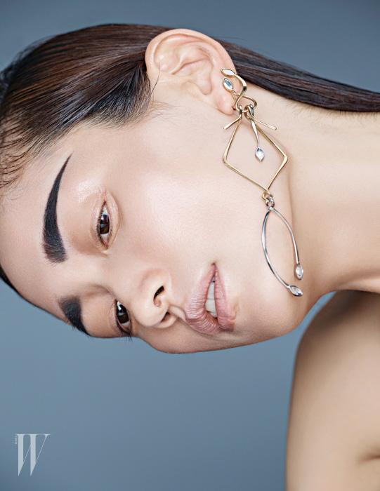 유연한 곡선미와 조형미가 돋보이는 대담한 크기의 메탈 귀고리는 Louis Vuitton 제품.