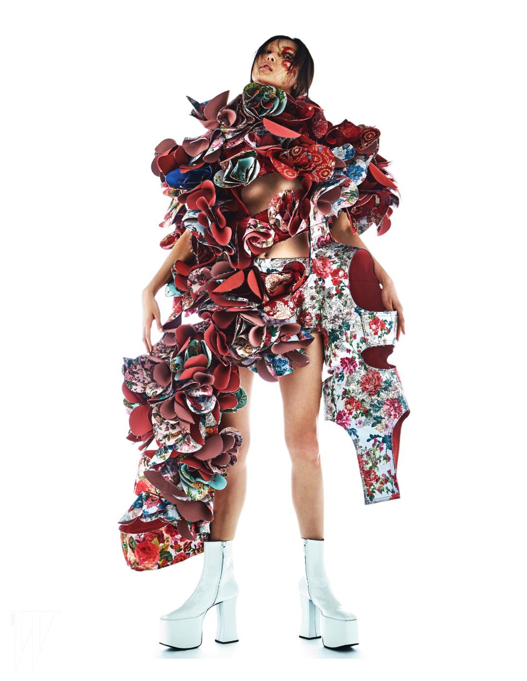 꽃을 테마로 만든 거대한 건축적인 드레스는 Comme des Garcons, 높은 플랫폼의 흰색 고고 부츠는 Saks Fifth Avenue Vintage by Angelica 제품.