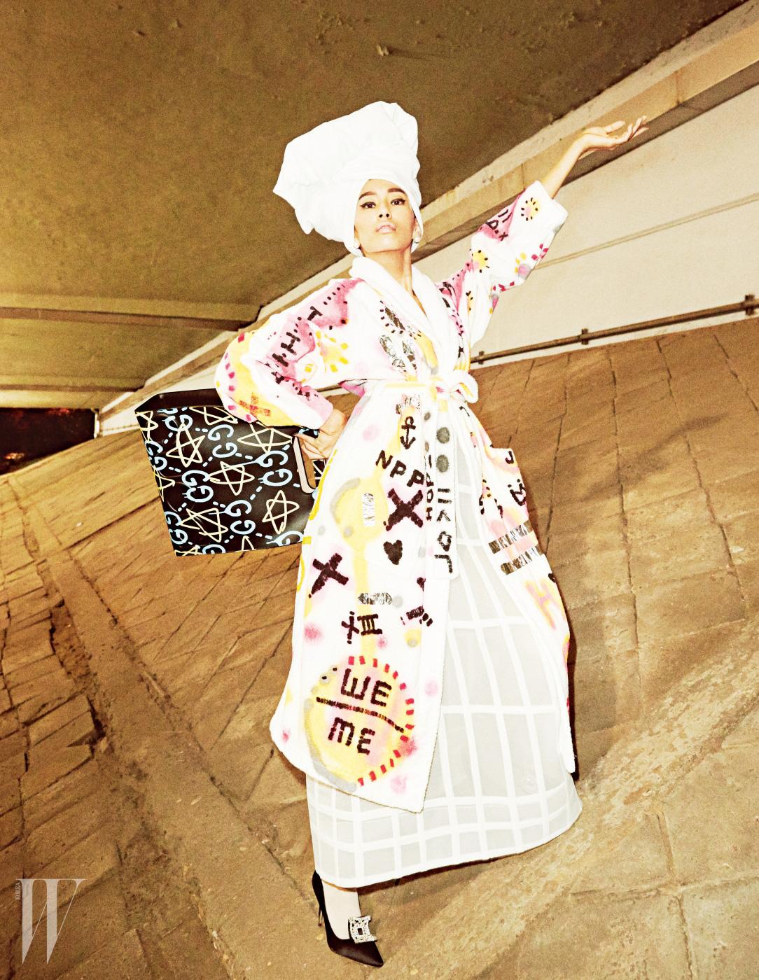 그라피티가 그려진 가운은 Supreme, 진주 귀고리는 Dior, 손에 들고 있는 구찌 고스트 프린트 라지 토트백은 Gucci, 중세풍의 우아한 새틴 슈즈는 Manolo Blahnik 제품.