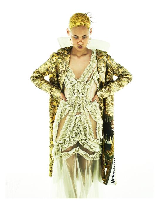 금빛 톤의 독특한 패턴이 눈에 띄는 자카드 코트는 Prada, 금색 러플 장식의 얇은 니트 롱 드레스는 YCH, 복고풍 안경테는 Jamie&Bell 제품.