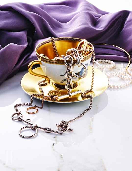 구조적인 고리 모양의 은 목걸이와 컵 위에 걸친 체인 팔찌, 컵받침 위에 놓인 반지, 커피잔과 받침은 모두 에르메스 제품.  가격 미정. 바닥에 놓인 진주 목걸이는 먼데이 에디션 제품. 18만원.