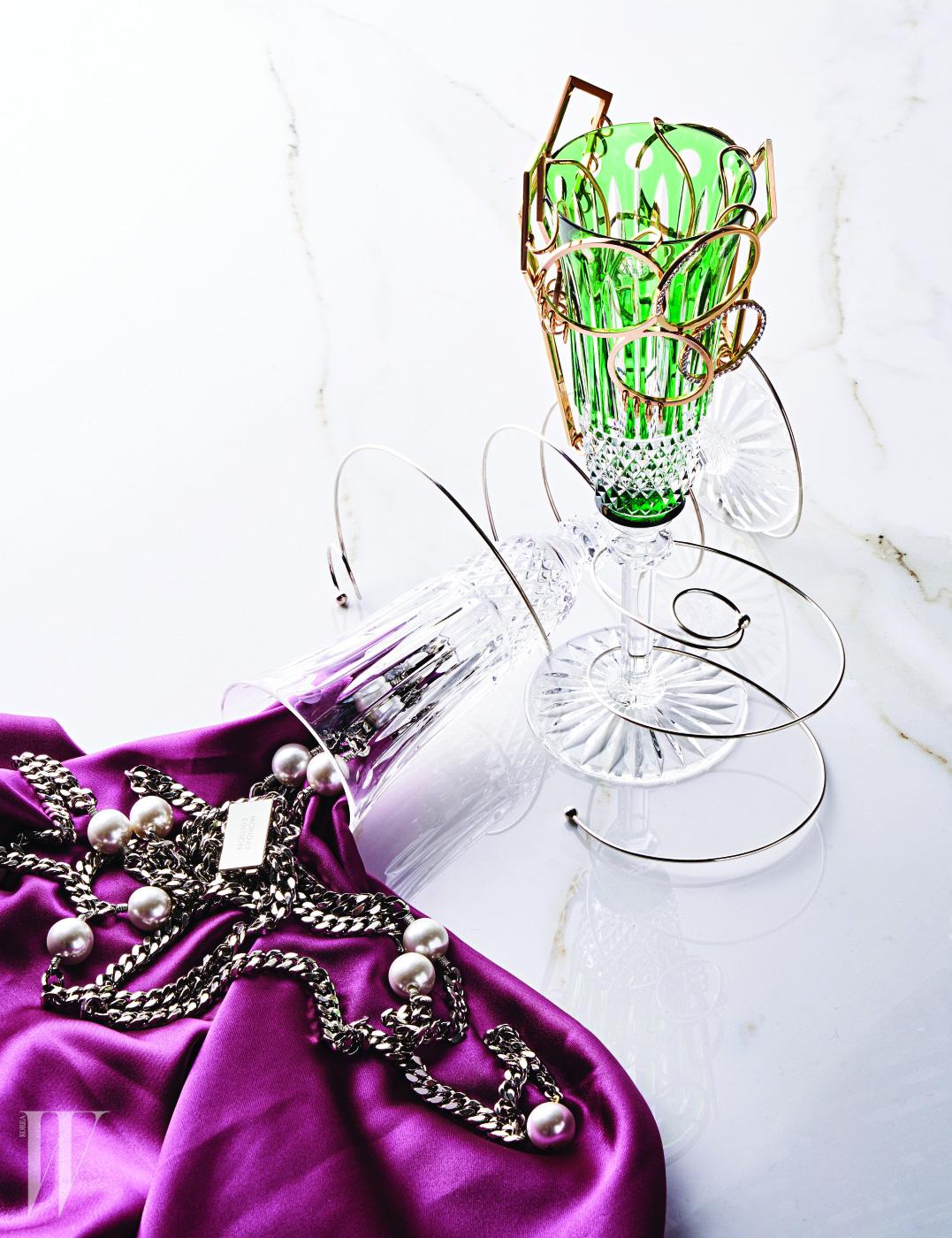 왼쪽부터 | 샴페인 잔에서 쏟아져 나온 진주 장식 체인 목걸이, 스프링이 연상되는 팔찌들은 모두 먼데이 에디션 제품.  각각 18만원, 18만원, 15만원. 초록색 샴페인 잔에 걸린 건축적이고 기하학적인 이어커프는 모두 김미혜 제품. 가격 미정.