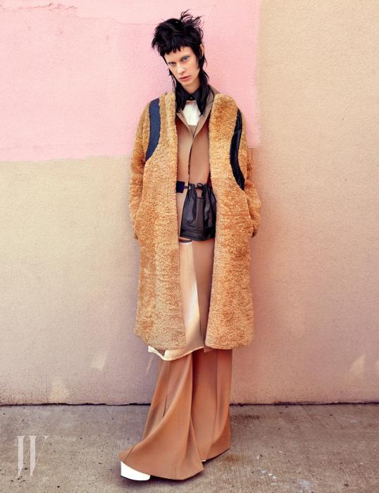 시어링 코트와 드레스, 셔츠, 와이드 팬츠와 가방은 Celine, 귀고리는 Louis Vuitton, 부츠는 Balenciaga 제품.