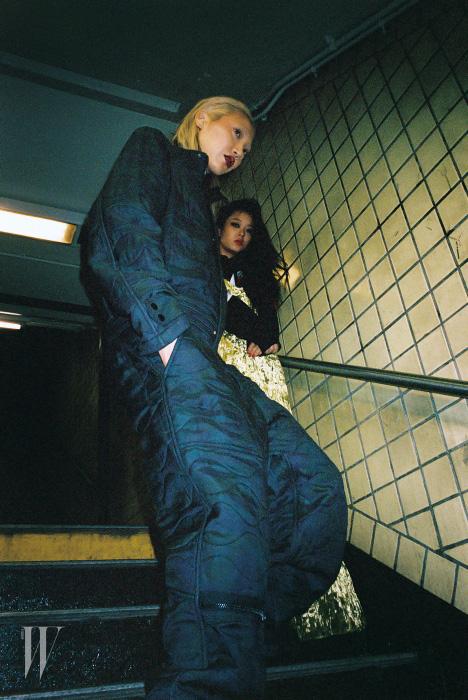 수주가 입은 퀼팅 처리된 남성용 점프슈트는 Public School 제품. 크리스티나가 입은 벨벳 소재 롱 드레스는 KYE 제품, 국기가 패치워크된 후드는 Supreme 제품으로 본인 소장품.