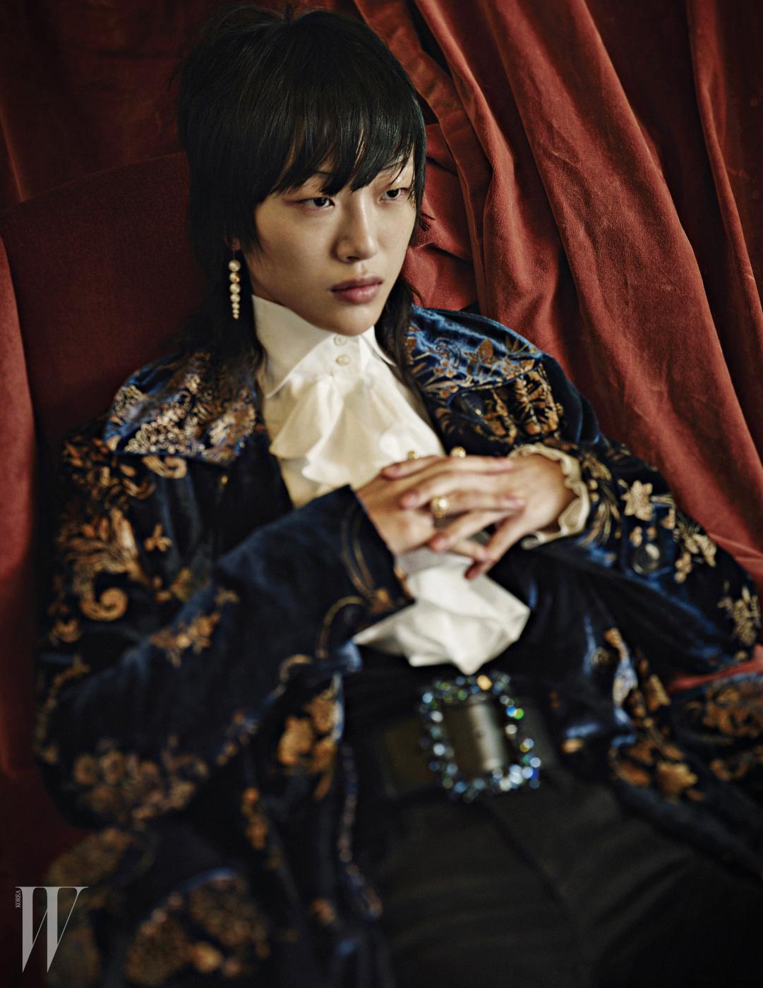 러플 장식의 화이트 셔츠, 로브 형태의 화려한 벨벳 코트는 Ralph Lauren Collection, 푸른색 크리스털 장식의 볼드한 버클이 돋보이는 가죽 벨트는 Escada, 조형적인 스트레치드 펄 귀고리와 반지는 모두 Tasaki 제품.