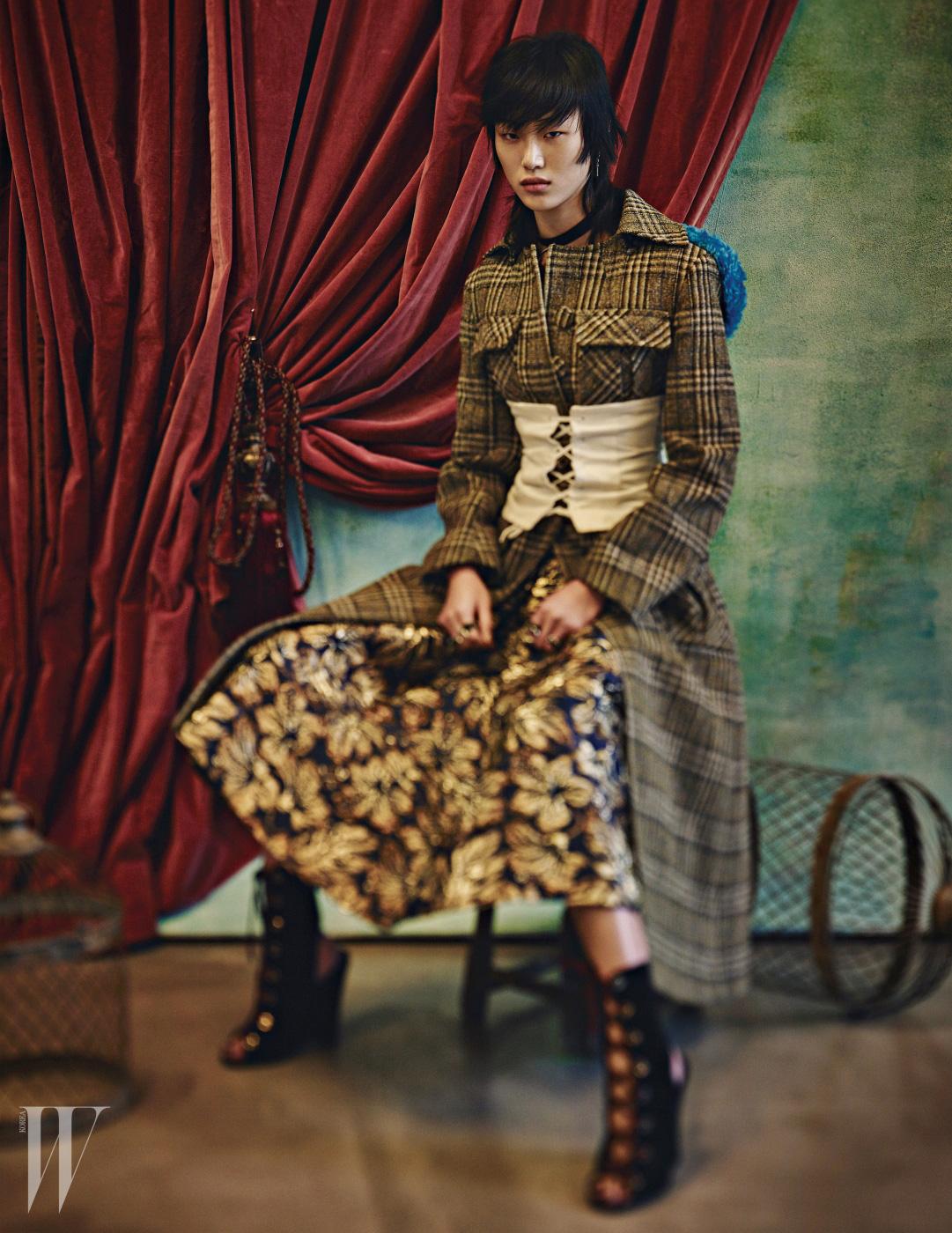 금빛 패턴이 화려한 드레스, 푸른색의 시어링 후드가 캐주얼한 악센트를 더하는 롱 코트, 뷔스티에, 벨벳 소재의 레이스업 부츠는 모두 Prada 제품.