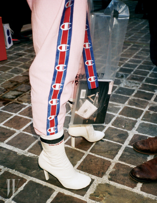 챔피온 로고 라이닝이 돋보이는 핑크색 트랙 팬츠와 스포티한 양말, 라이터 굽 앵클부츠는 모두 Vetements 제품.