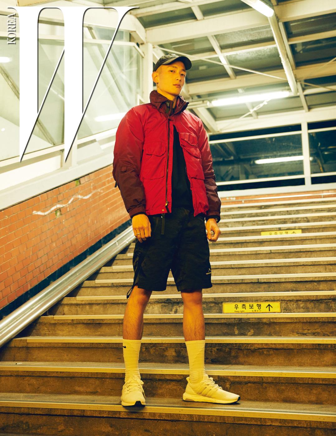 붉은색 점퍼는 Acronym, 옆선의 스트링 장식이 특징인 쇼츠는 Silencion, 검정 스웨트 셔츠는 Supreme, 흰색 스니커즈는 Adidas 제품.