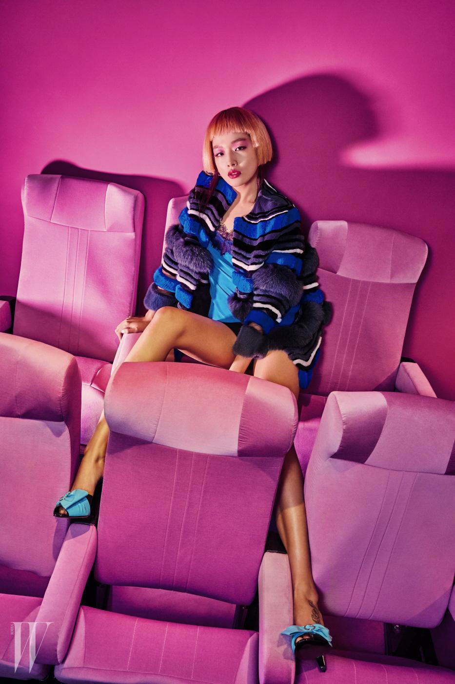 퍼 코트는 Fendi, 레이스 톱은 Escada, 하늘색 리본 장식 뮬은 Prada 제품.