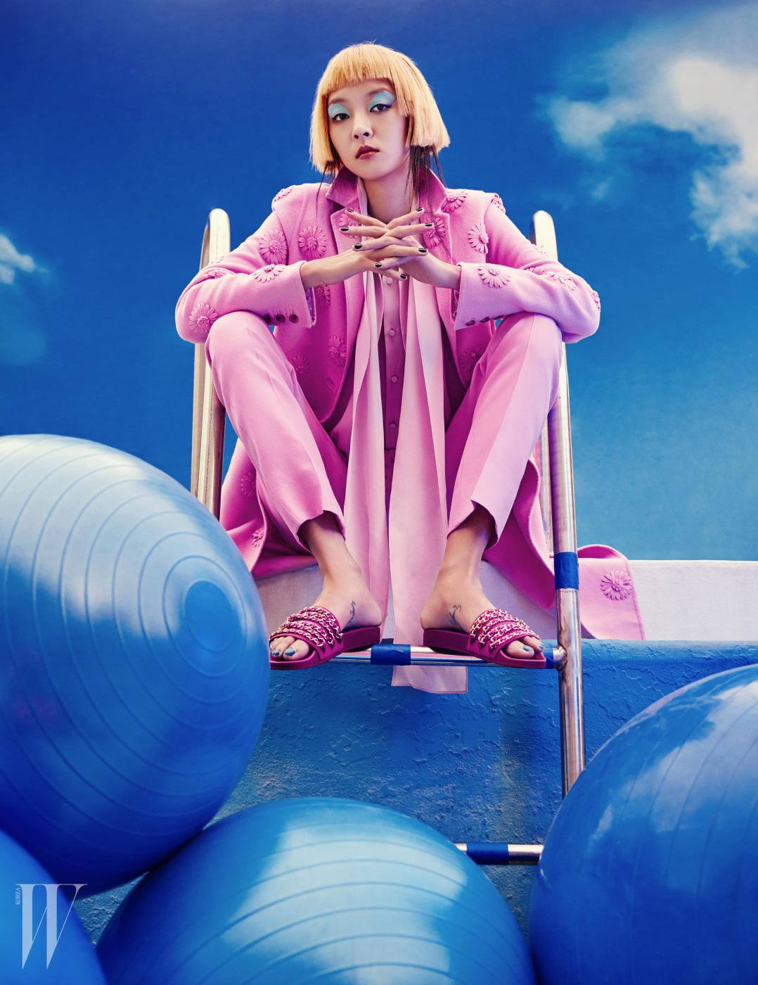 입체적인 꽃무늬 코트, 스카프 장식 블라우스, 팬츠는 모두 Valentino, 체인 장식 슬리퍼는 Chanel 제품.