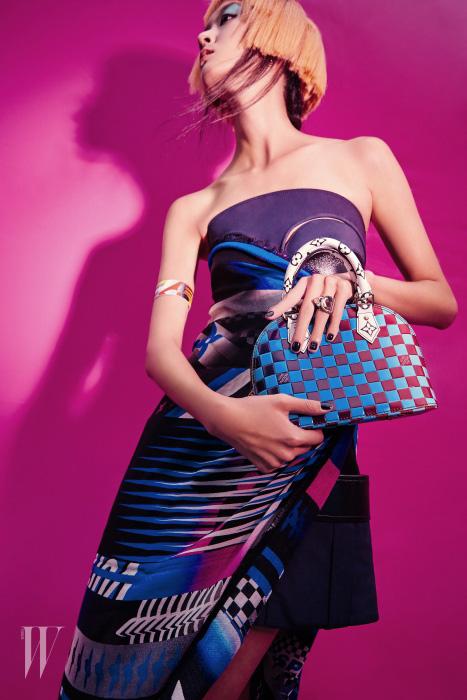가죽 미니 드레스, 드레스 위에 둘러 연출한 스피디 프린트 스카프, 백, 팔에 두른 밴드와 반지는 모두 Louis Vuitton 제품.