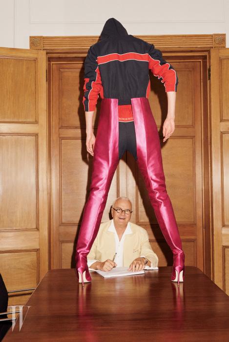 런던에 위치한 자신의 사무실에서 포즈를 취한 마놀로 블라닉. 그의 앞에 선 모델이 신은 것이 바로 베트멍과 협업한 화제의 장화 스타일 사이하이 부츠다.