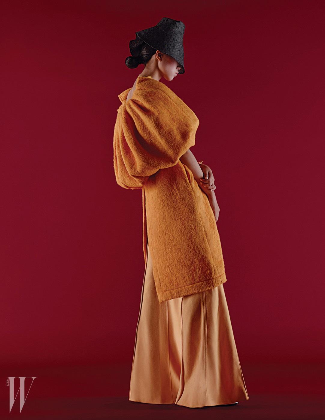 케이프 장식이 가미된 코트와 통 넓은 팬츠는 모두 셀린 제품. 가격 미정. 모자는 신저 제품. 가격 미정.