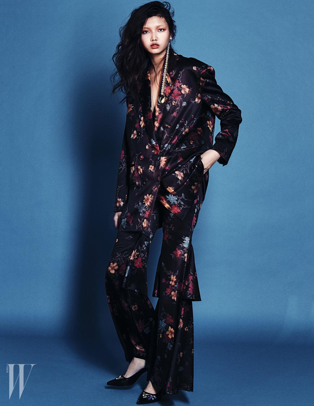 큼직한 꽃무늬 실크 더블 재킷과 티어드 절개 라인의 팬츠 슈트, 자수가 들어간 검은색 뮬과 금색 드롭 귀고리는 모두 The Centaur 제품.