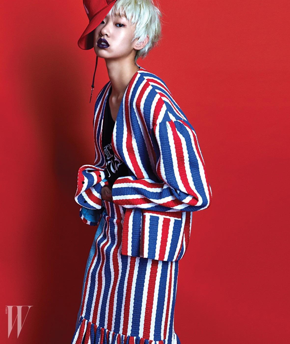 빨강, 하양, 파랑이 섞인 스트라이프 재킷과 미디 길이 스커트, 로고 프린트 티셔츠, 빨강 스냅백과 드롭 귀고리는 모두 Lucky Chouette 제품.