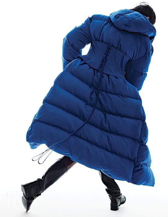 코르셋 장식의 파란색 롱 패딩 점퍼는 푸시버튼 제품. 가격 미정. 클래식한 부츠는 랄프 로렌 제품. 가격 미정.