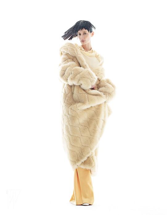 다이아몬드 무늬로 깎은 미색의 맥시 퍼 코트는 87mm 제품. 가격 미정. 안에 입은 터틀넥과 노란색 팬츠는 셀린느 제품. 가격 미정. 하얀색 슈즈는 마르니 제품. 가격 미정.