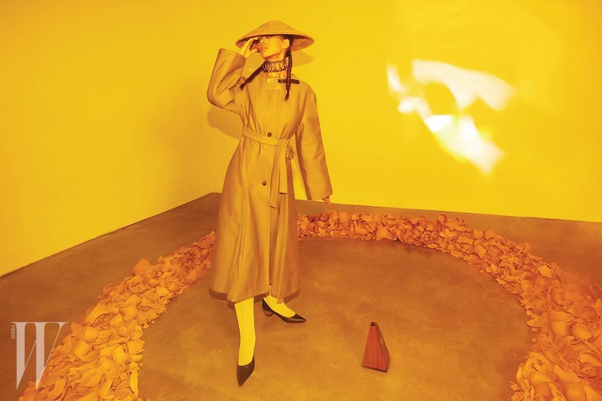 베이지색 누빔 코트, 금속 초커, 가죽이 장식된 가방 모양의 펜던트는 모두 로에베 제품. 가격 미정. 스웨이드 소재의 미들 굽 부츠는 마르니 제품. 가격 미정모. 자는 에디터 소장품.