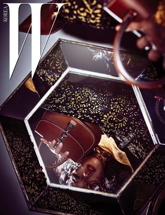 루이 비통의 여행 정신을 보여주는 체인 장식이 특징인 '체인 잇' 가방, 반짝이는 금색 톱, 화려한 금장 장식이 떠오르는 꽃무늬 팬츠와 빨간색 부츠는 모두 Louis Vuitton 제품.