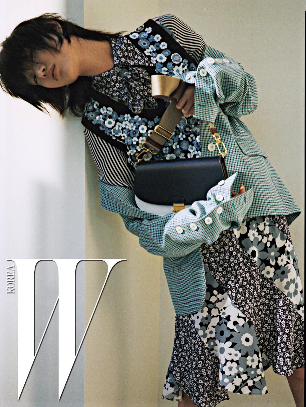 체크 패턴 테일러드 재킷, 꽃과 줄무늬 프린트가 어우러진 셔츠, 꽃 장식 베스트, 두 가지 꽃무늬가 어우러진 스커트, 간결한 숄더백은 모두 Michael Kors Collection 제품.