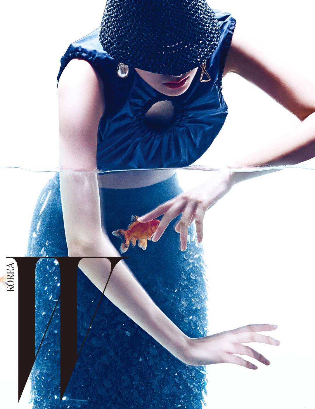 컷아웃 장식과 주름이 가미된 파란색 톱, 물고기 비늘이 연상되는 검은색 펜슬 스커트, 검은색 라피아 소재 모자, 바로크 진주와 물고기 모양 귀고리는 모두 Sportmax 제품.
