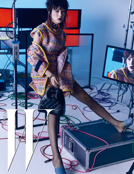 소매의 벨크로 장식과 노란색 라이닝이 돋보이는 트위드 재킷, 미니 드레스, 브랜드의 새로운 아이코닉 백인 가브리엘 백, 초커로 짧게 연출한 로고 장식 목걸이, 투톤의 뮬은 모두 Chanel 제품.