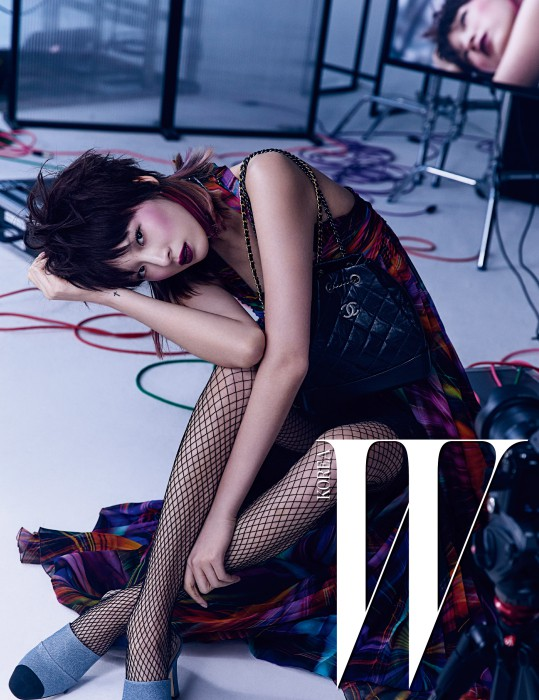 화려한 프린트의 홀터넥 롱 드레스와 이너로 매치한 검정 레이스 스커트, 퀼팅 가죽 소재의 가브리엘 백, 투톤 뮬은 모두 Chanel 제품.