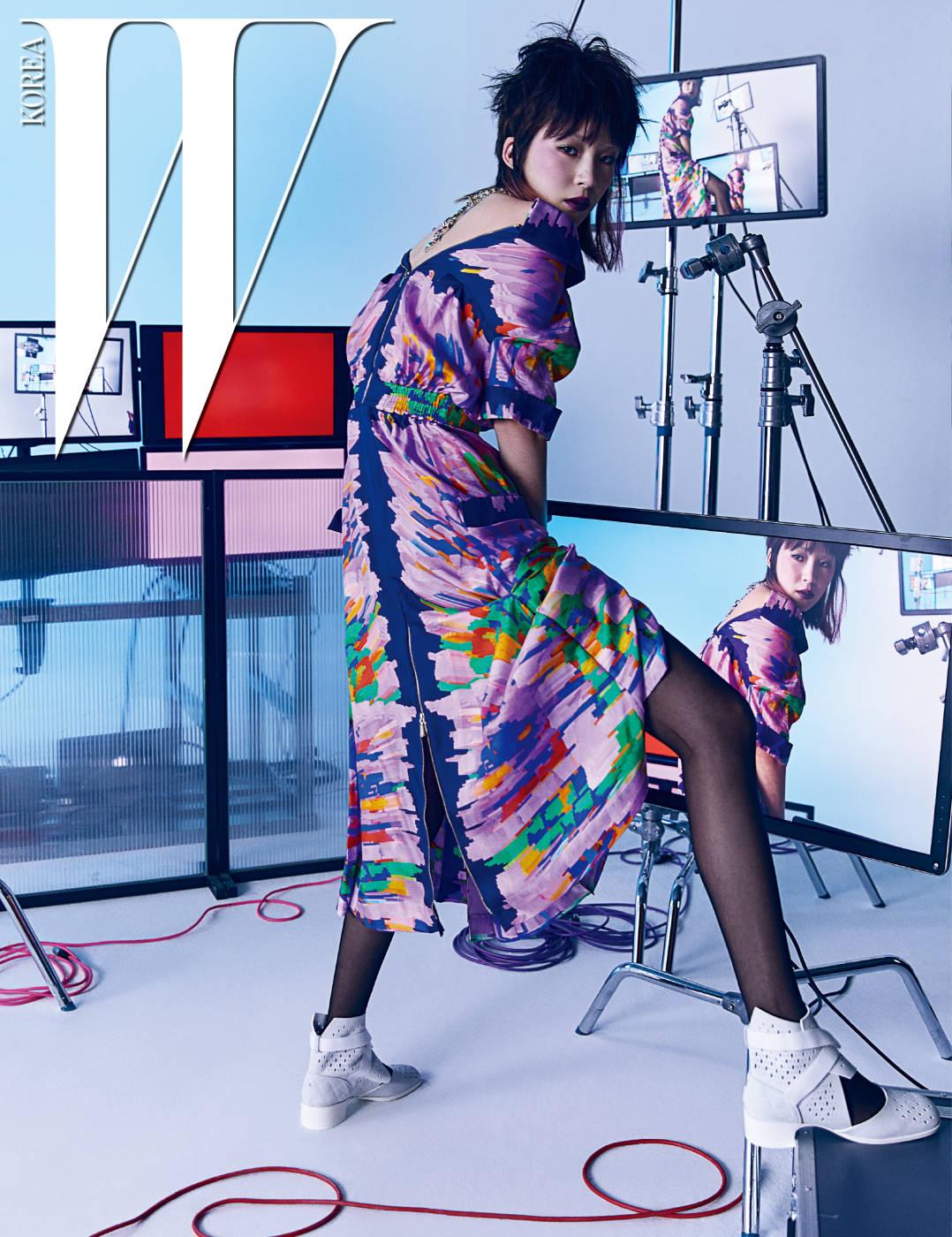 화려한 프린트가 강렬한 집업 톱과 스커트, 십자가 모티프의 펜던트 목걸이, 엘라스틱 밴드 장식의 메시 슈즈는 모두 Chanel 제품.