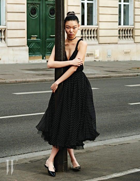 네크라인이 깊게 파인 잔잔한 물방울 무늬 드레스와 플랫 슈즈, 초커는 모두 Dior 제품.