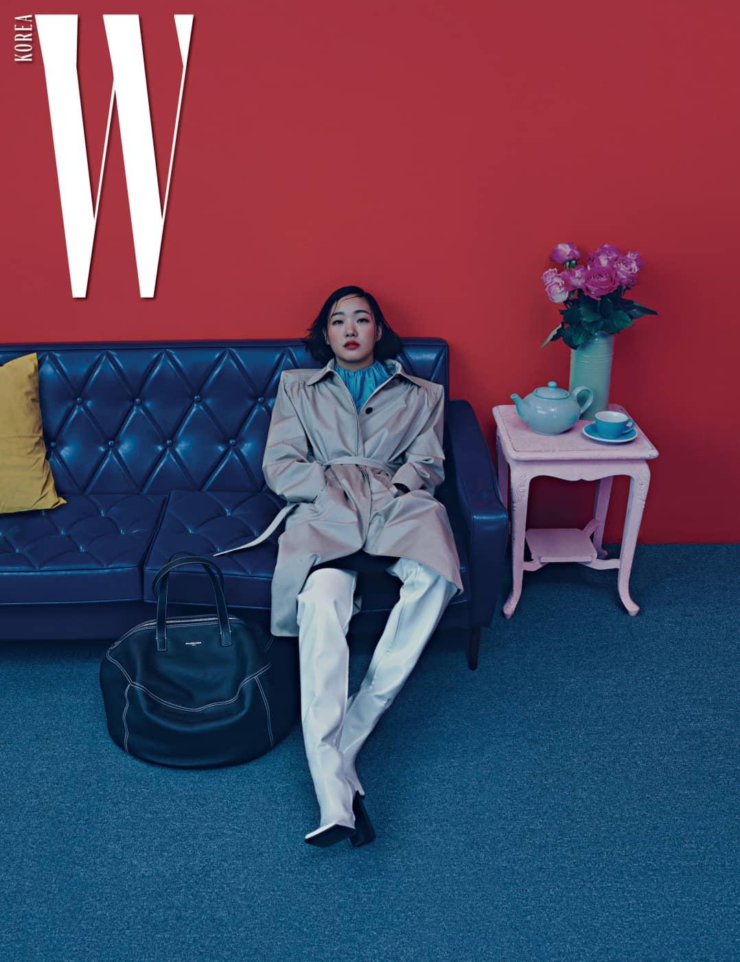 어깨를 강조한 실루엣이 돋보이는 트렌치코트, 푸른색 톱과 슬립 스커트, 흰색 가죽 부츠, 그리고 에어 호보백 (Air Hobo Bag)은 모두 Balenciaga 제품.