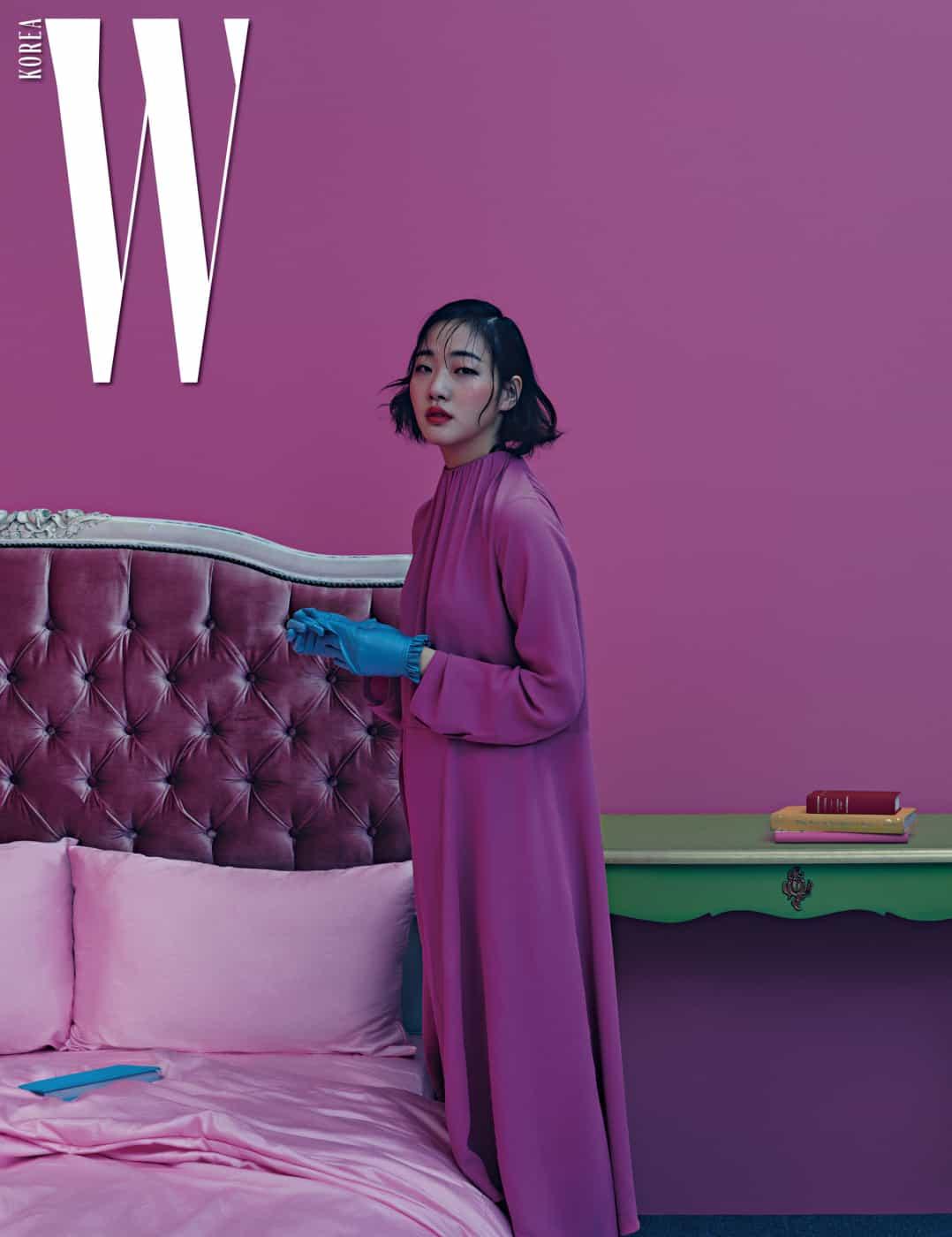 주름 장식의 하이 네크라인으로 레트로 무드를 가미한 분홍색 드레스와 러플 장식의 푸른색 장갑은 Balenciaga 제품.