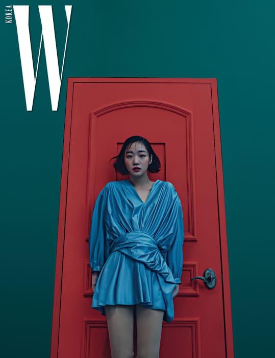 동그란 어깨 실루엣과 주름이 우아함을 더하는 푸른색 드레스, 스판덱스 소재의 팬츠 형태 부츠는 Balenciaga 제품.