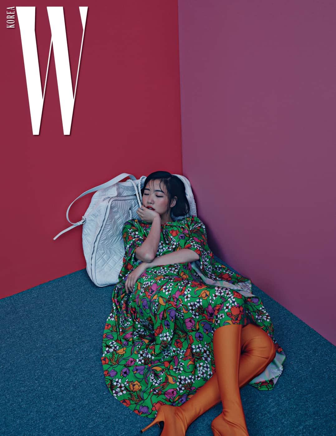 풍성한 볼륨감과 꽃무늬가 돋보이는 가스펠 드레스와 주황색 스판덱스 소재 부츠, 흰색의 자이언트 블랭킷 백(Blanket Bag)은 모두 Balenciaga 제품.