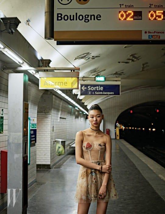 코르셋 형태의 디자인이 인상적인 비즈 장식 미니 드레스와 초커, 귀고리, 로고 장식 팔찌와 반지는 모두 Dior 제품.