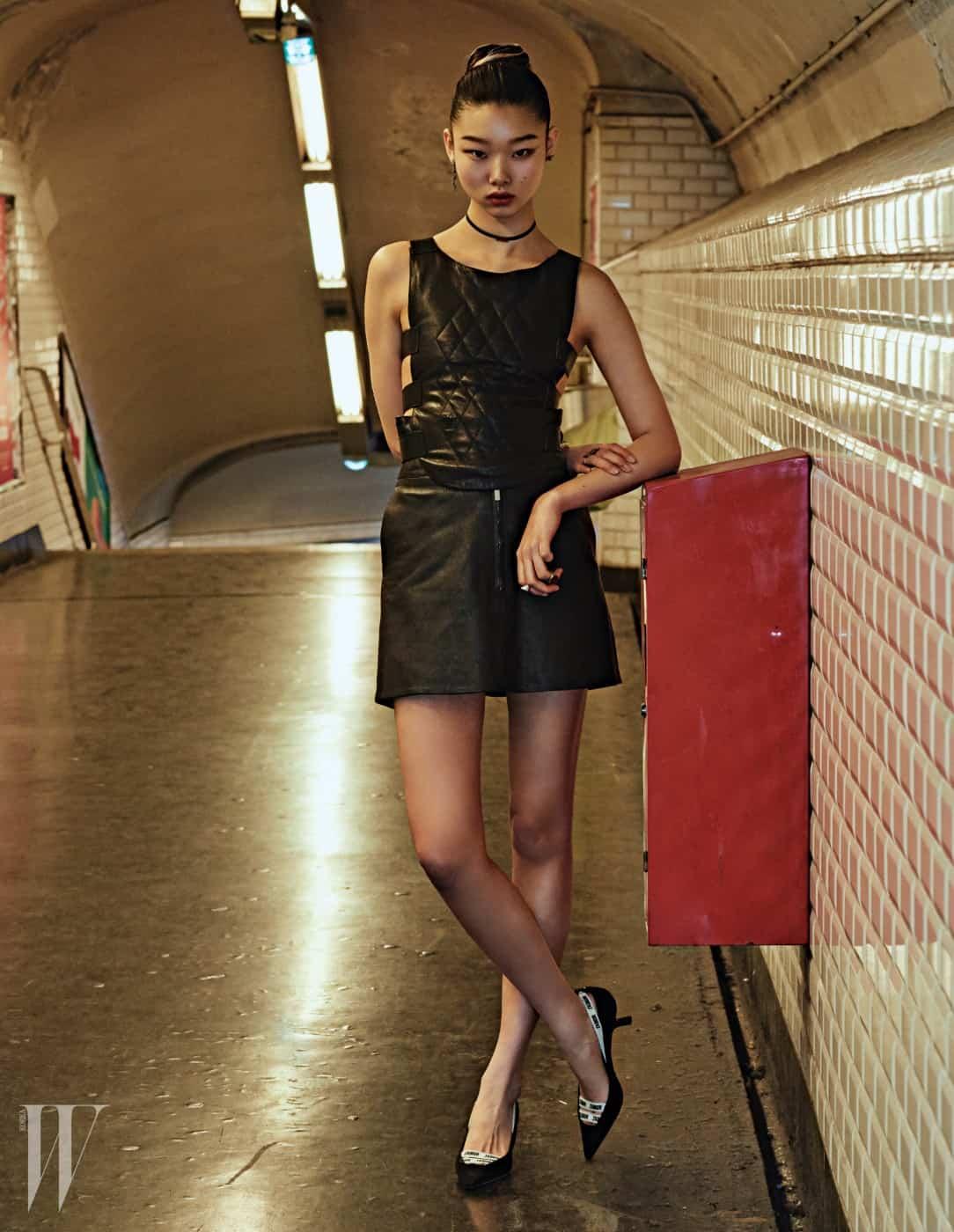 펜싱 베스트를 연상시키는 가죽 톱과 미니스커트, 밴드 스트랩 슈즈, 초커, 귀고리, 반지는 모두 Dior 제품.