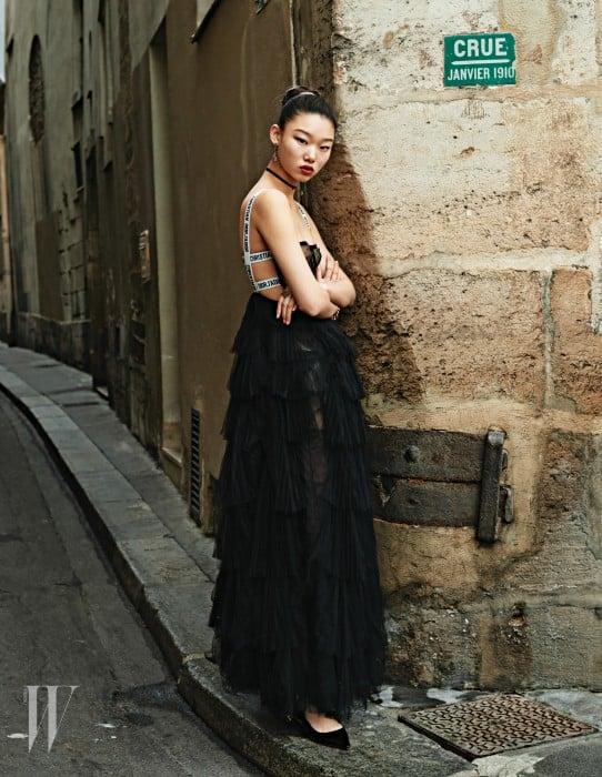 스포티한 밴드형 스트랩과 여성스러운 소재의 조합이 인상적인 티어드 드레스, 초커와 귀고리, 슈즈는 모두 Dior 제품.