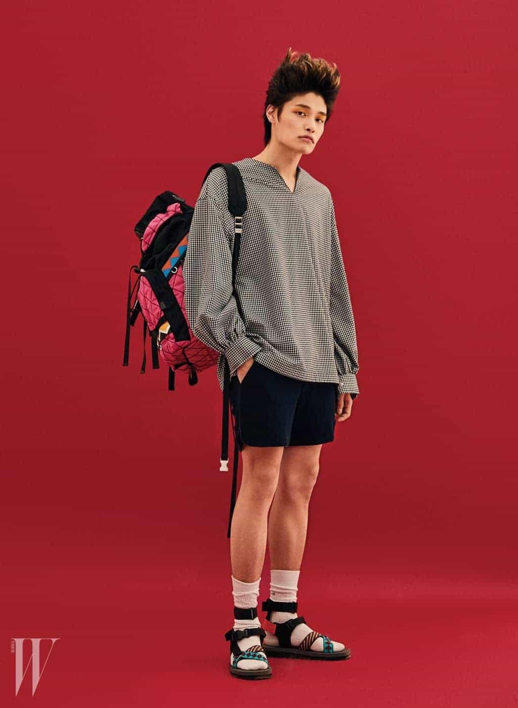 격자무늬 셔츠 블라우스는 오디너리 피플 제품. 가격 미정. 쇼츠는 펜디 제품. 가격 미정. 양말은 톰 브라운 제품. 가격 미정. 프린트 스트랩 장식 스포츠 샌들은 60만원대. 비비드한 색감의 산악 모티프 백팩은 2백20만원대. 모두 프라다 제품.
