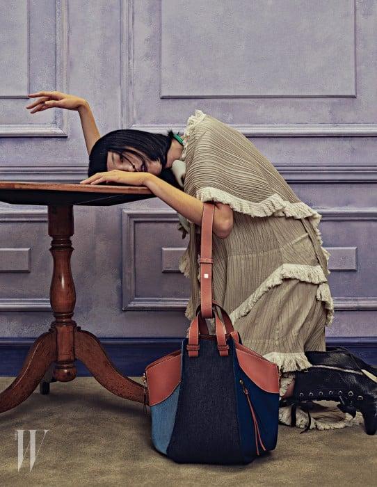 베이지 숄 주름 장식의 티어드 드레스, 멀티 데님 해먹 백(Multi Denim Hammock Bag), 목걸이로 연출한 흰색 코르사주 장식의 가죽 팔찌, 검정 레이스업 앵클부츠는 모두 Loewe 제품.