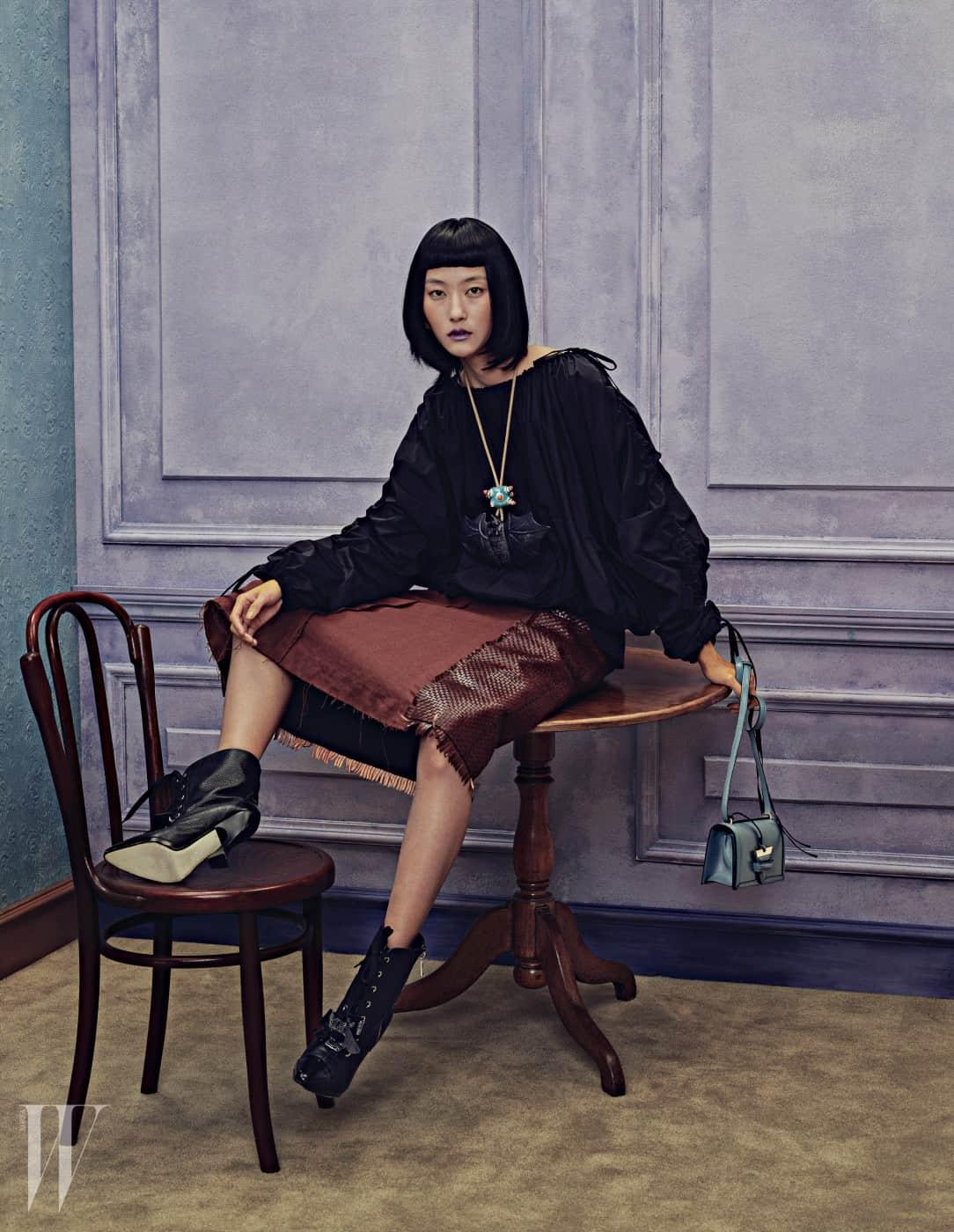 풍성한 실루엣이 돋보이는 벌룬 톱, 가죽 패널 장식의 갈색 스커트, 박쥐 모티프의 아티스틱한 펜던트 목걸이, 스톤 블루 색상의 바르셀로나 스몰 백(Barcelona Small Bag), 검정 레이스업 앵클부츠는 모두 Loewe 제품.