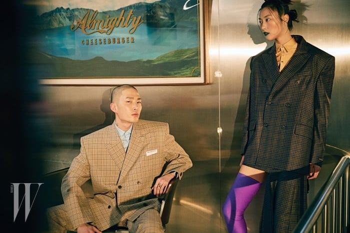 노마한이 입은 체크무늬 재킷, 팬츠, 셔츠, 박지혜가 입은 박시한 블레이저와 비대칭 스커트, 스판덱스 소재 셔츠와 부츠는 모두 Balenciaga 제품.