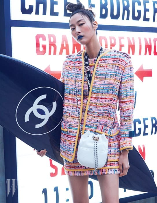 판타지 트위드 재킷, 미니 드레스, 주머니 모양의 가브리엘 백, 로고 프린트 목걸이, 진주 장식 목걸이, 서프보드는 모두 Chanel 제품.